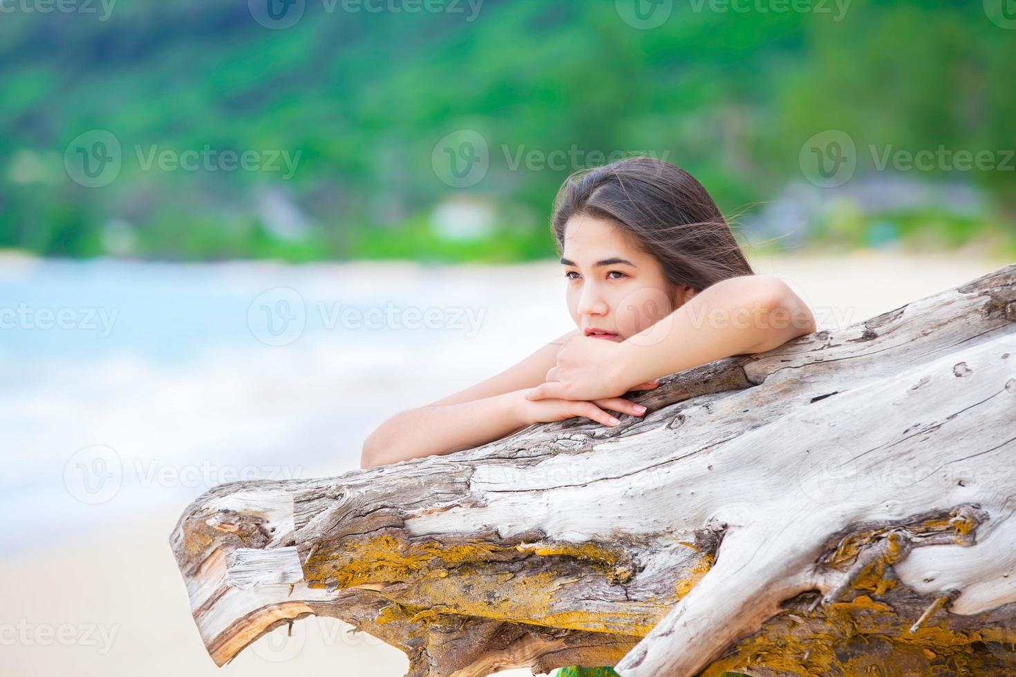 Beautiful teen girl on beach praying by driftwood log photo