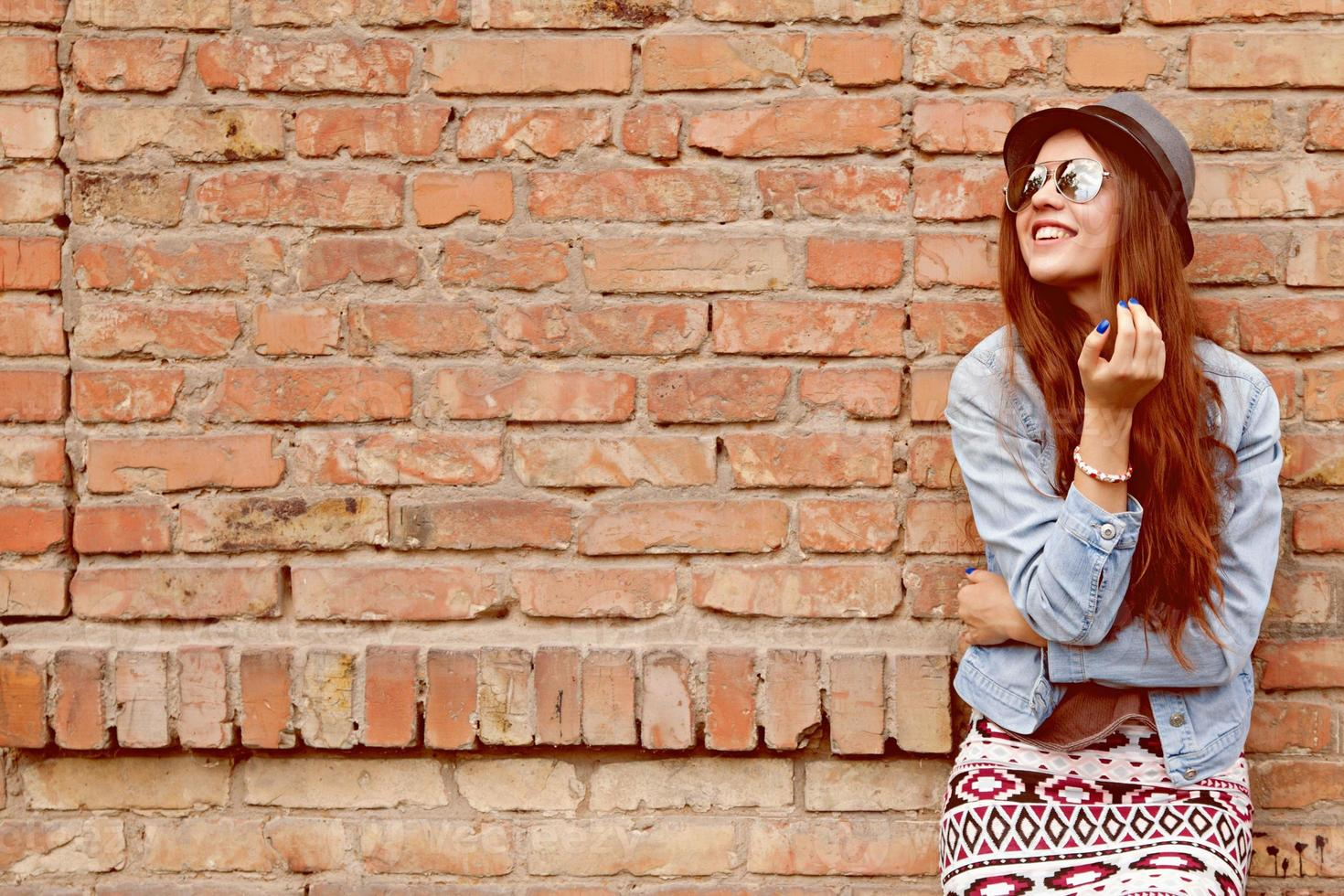 hermosa linda chica adolescente sonriendo cerca de la pared de ladrillo foto