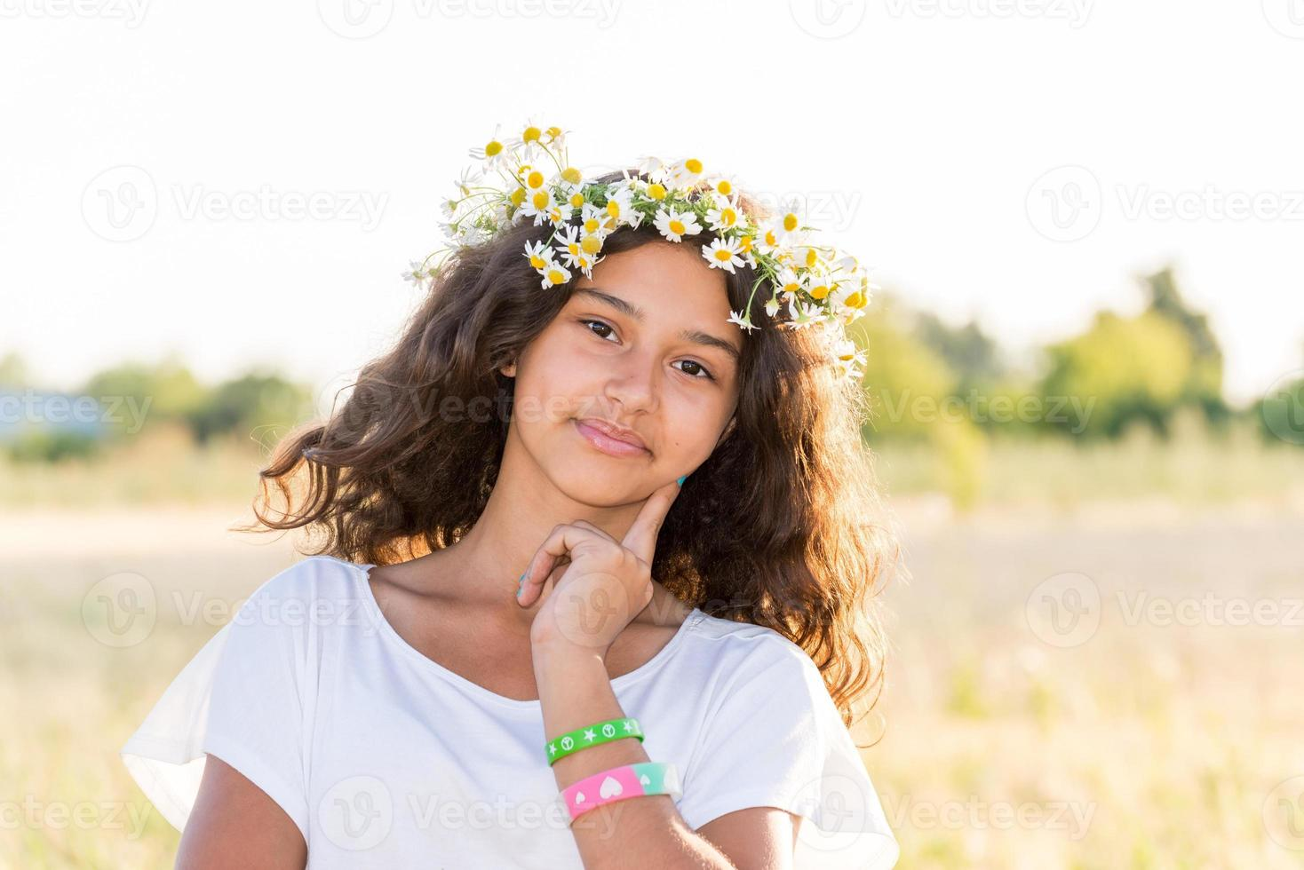 Teen girl with a wreath of daisies in   field photo