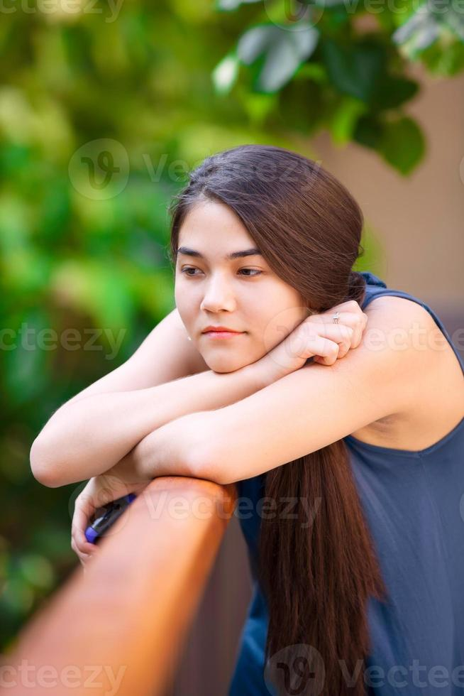 Chica adolescente birracial con teléfono celular, apoyándose en la baranda, pensando foto