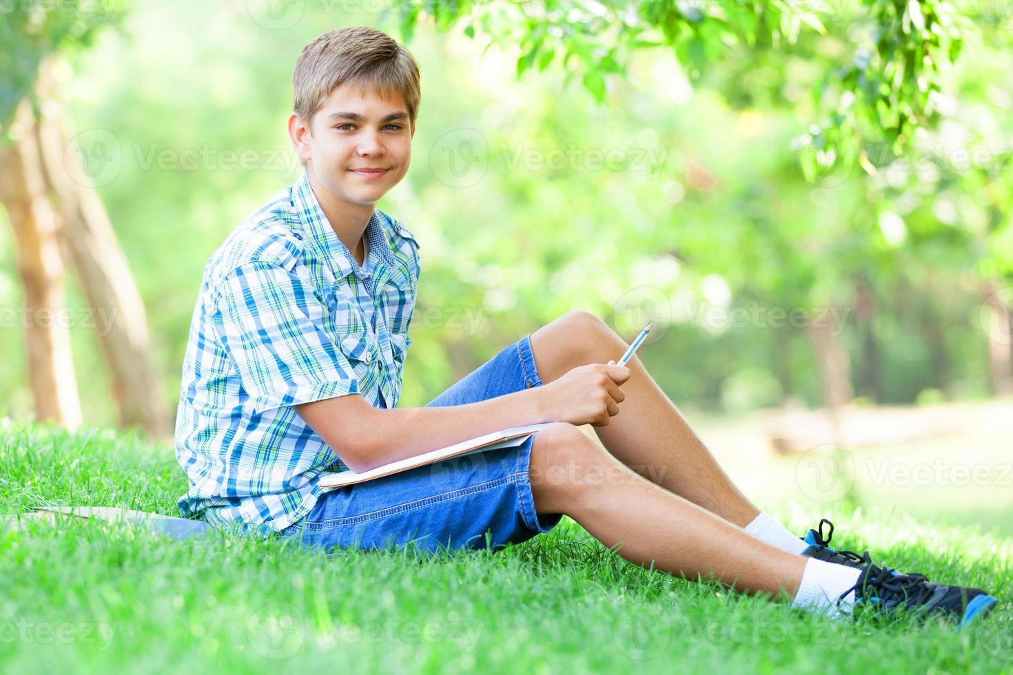 Muchacho adolescente con libros y cuaderno en el parque. foto