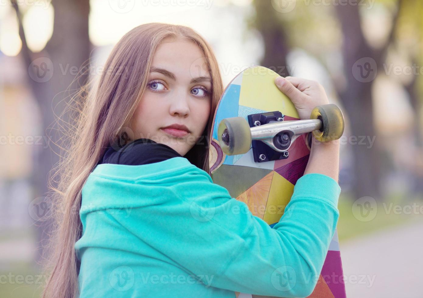 Teenage girl with skateboard photo