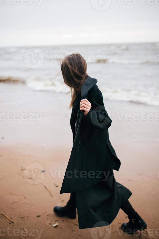 Girl walking on the sea shore photo