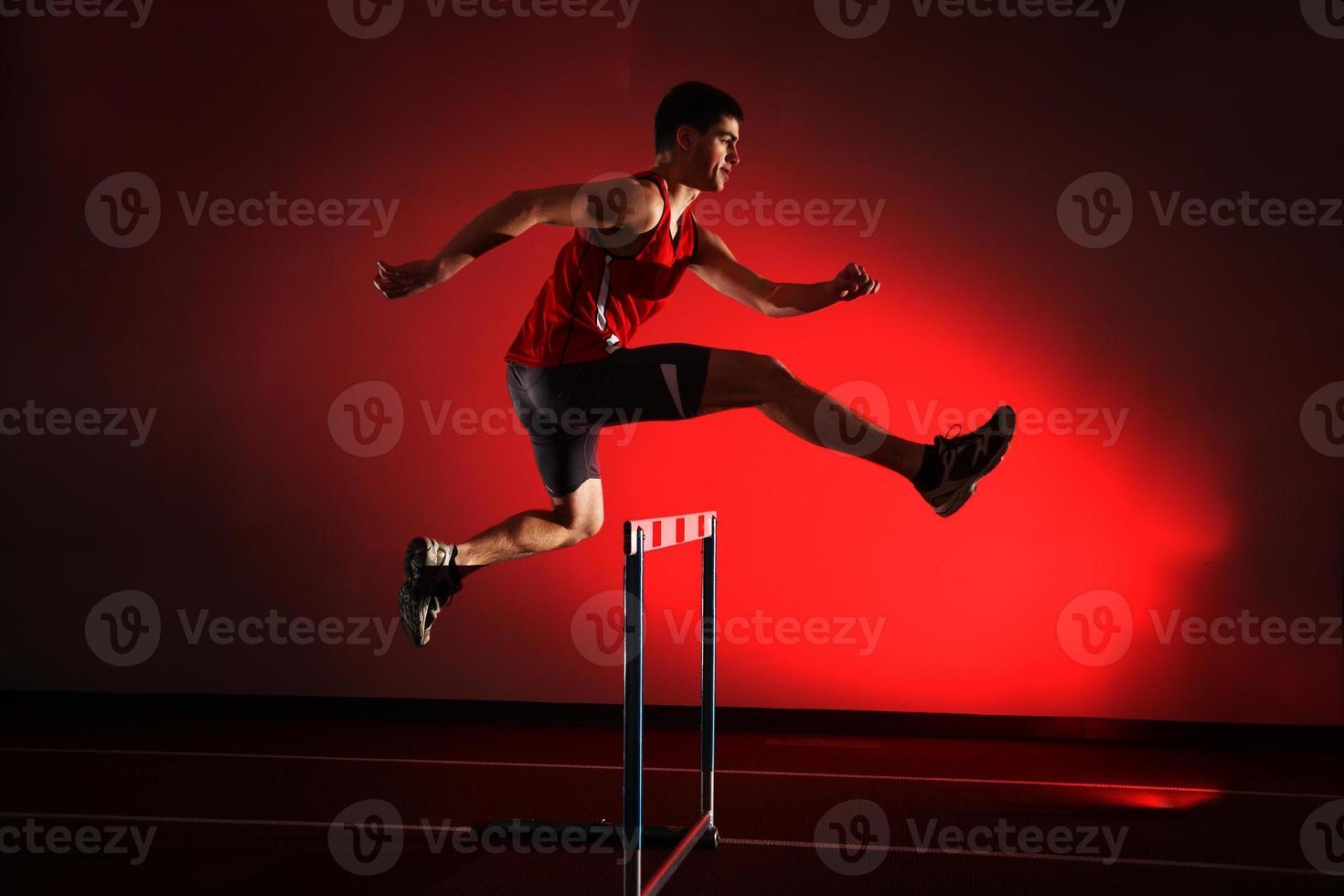 Atleta corriendo obstáculos aislados sobre fondo rojo. foto