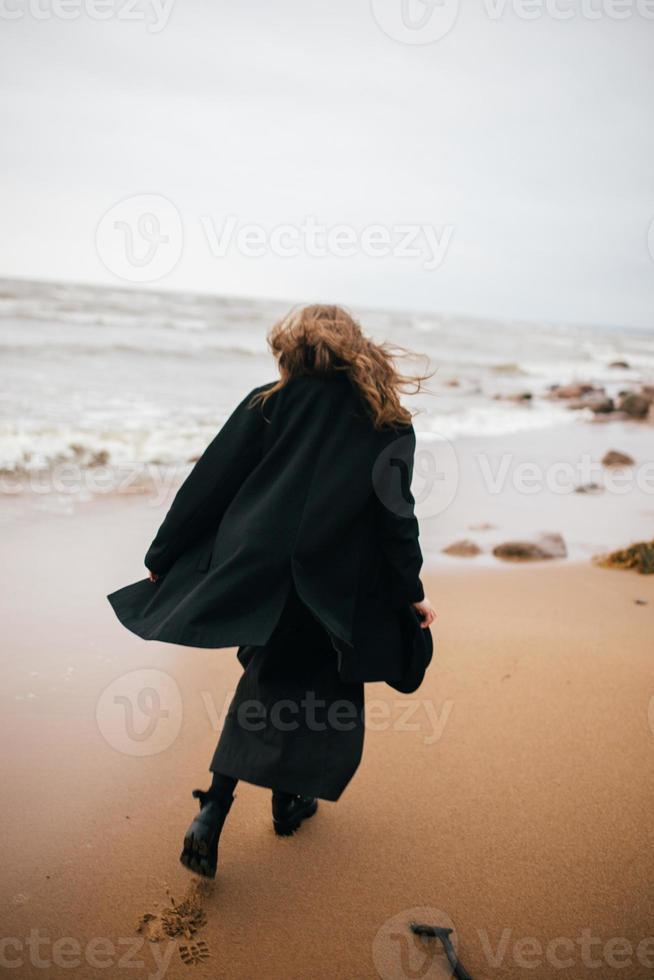 niña caminando por la orilla del mar foto