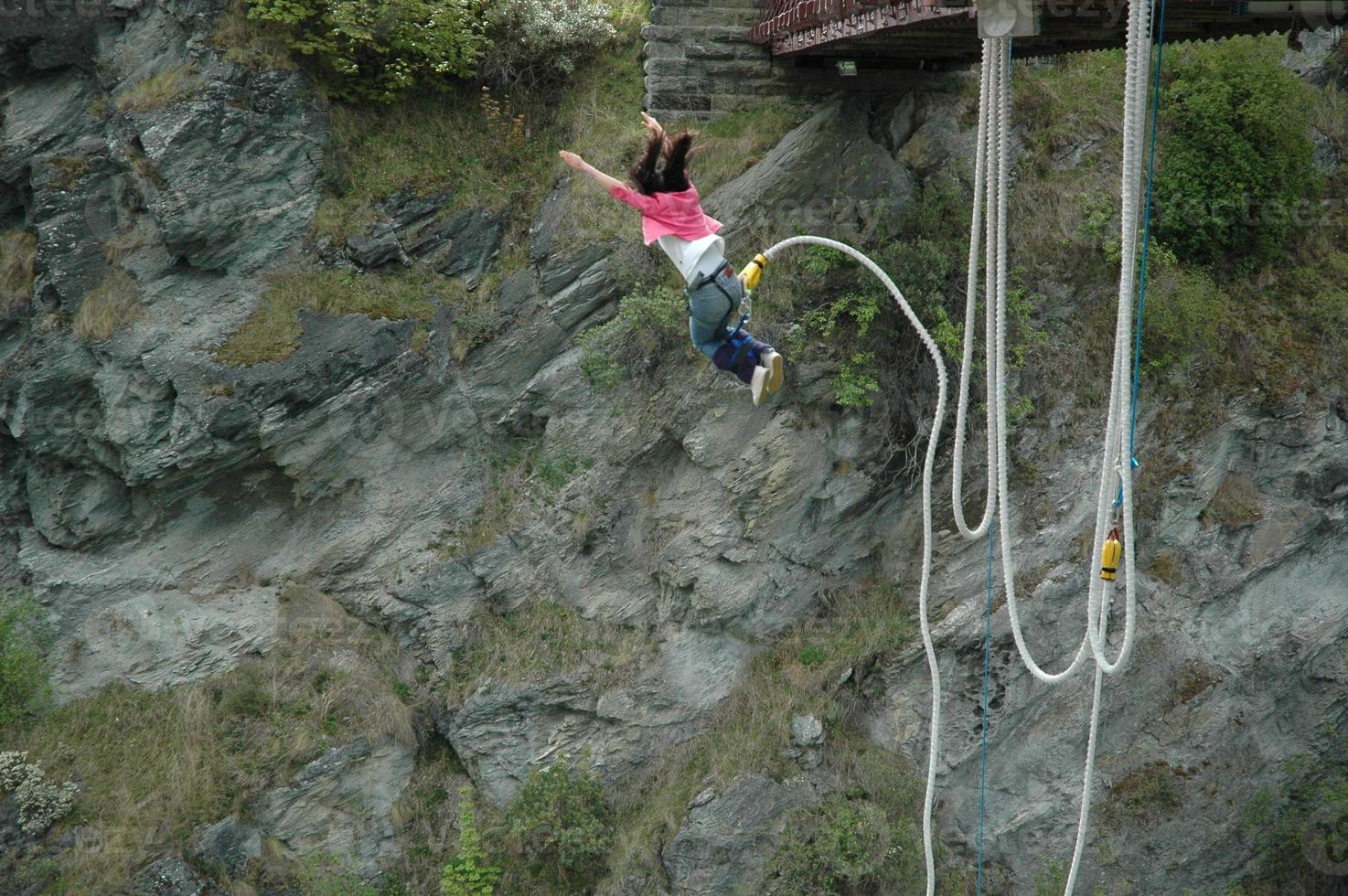 A woman bungee jumping off of a bridge photo