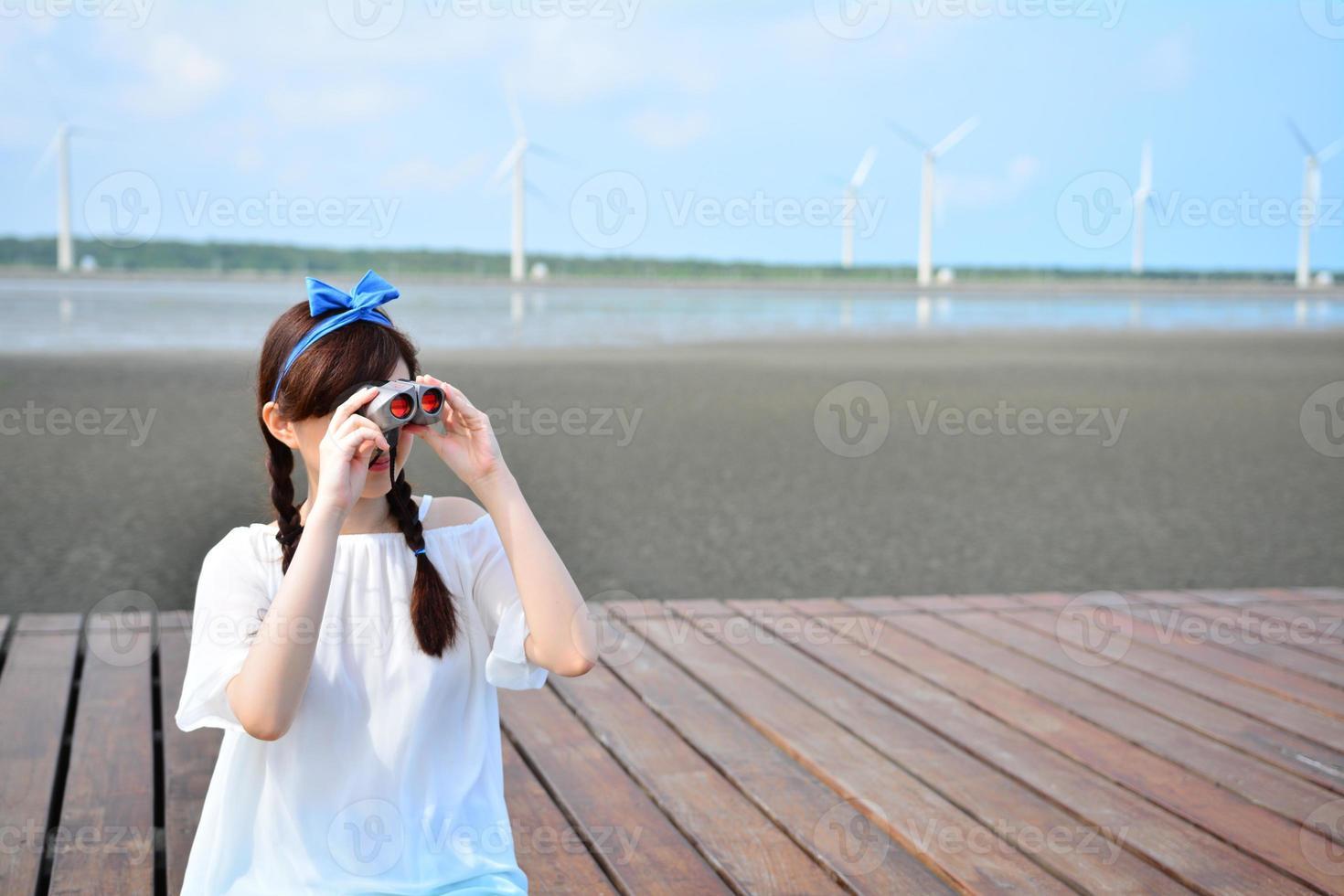 Teenage girl lifted up binoculars photo