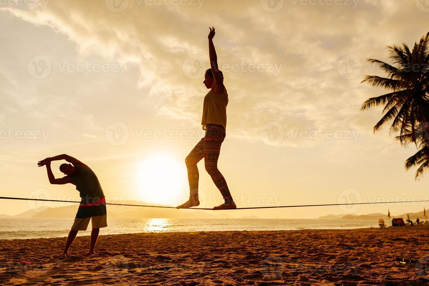 teenagers balance on slackline silhouette photo