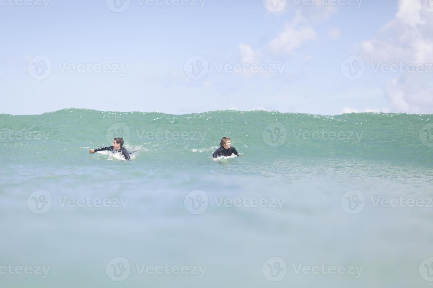 Teenage boys paddling with surfboard photo
