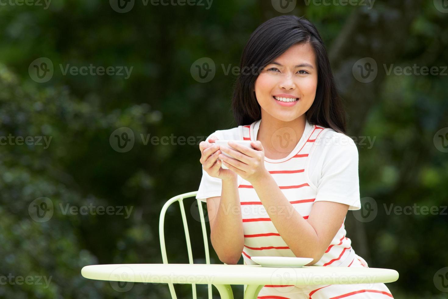Adolescente con bebida caliente en el café al aire libre foto
