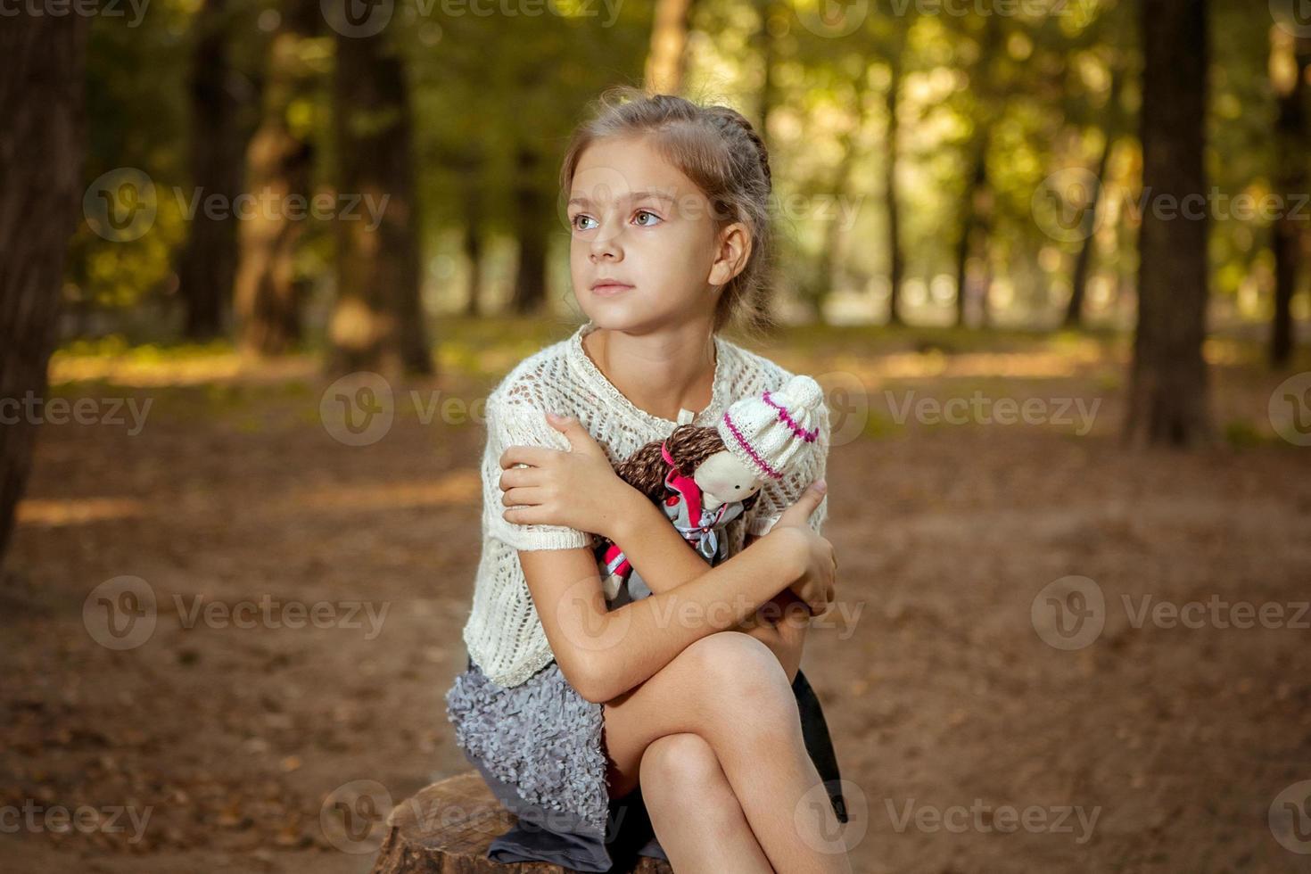 niña encantadora en bosque con muñeca foto