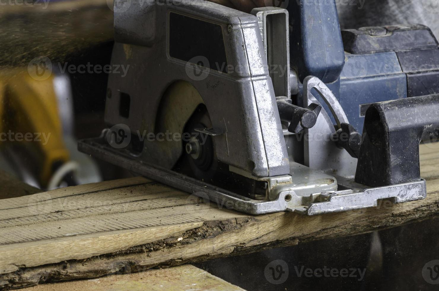 Male carpenter is cutting wood. photo