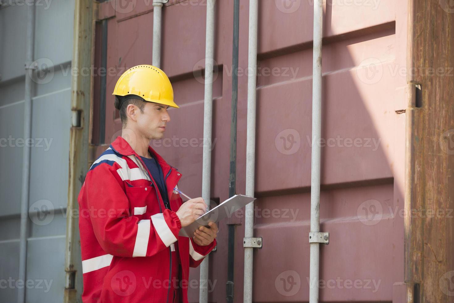 trabajador de sexo masculino que inspecciona el contenedor de carga foto