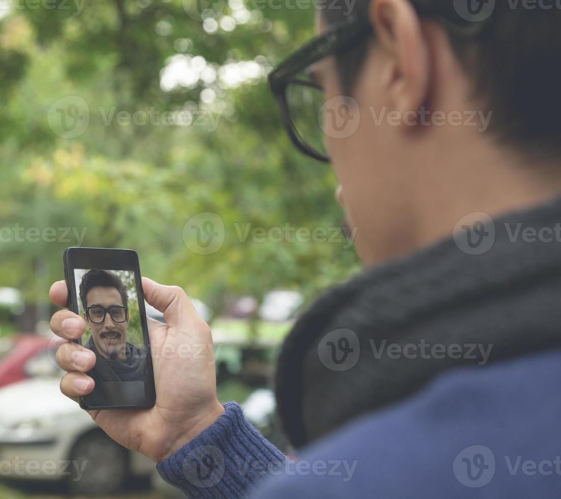 hombre atractivo con bigotes tomando selfie foto