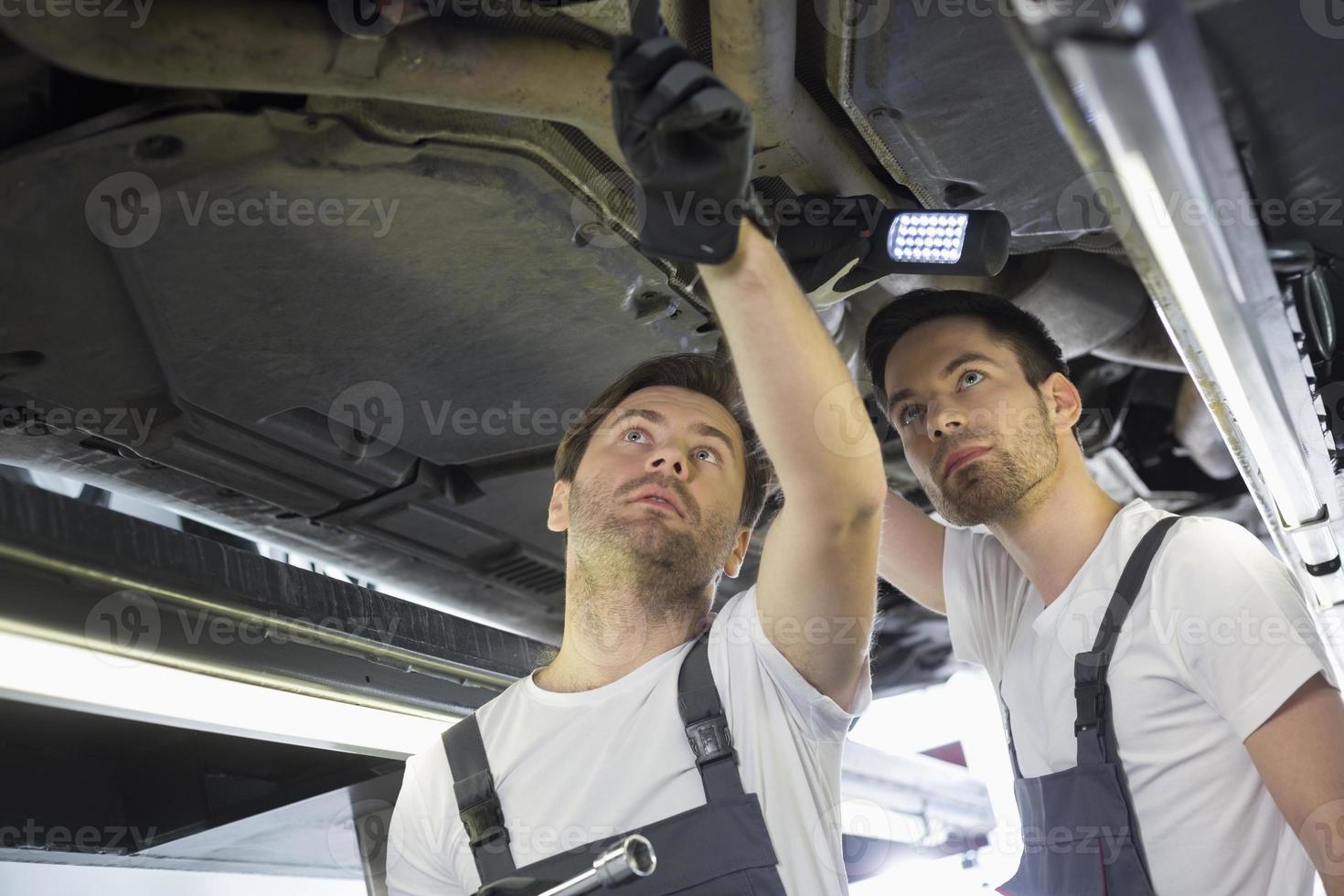 Male mechanics examining car in workshop photo
