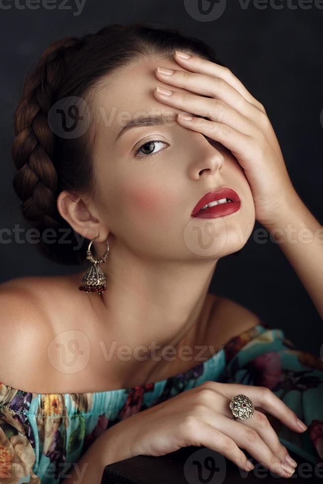 Retrato de una hermosa joven con joyas hechas a mano posando foto