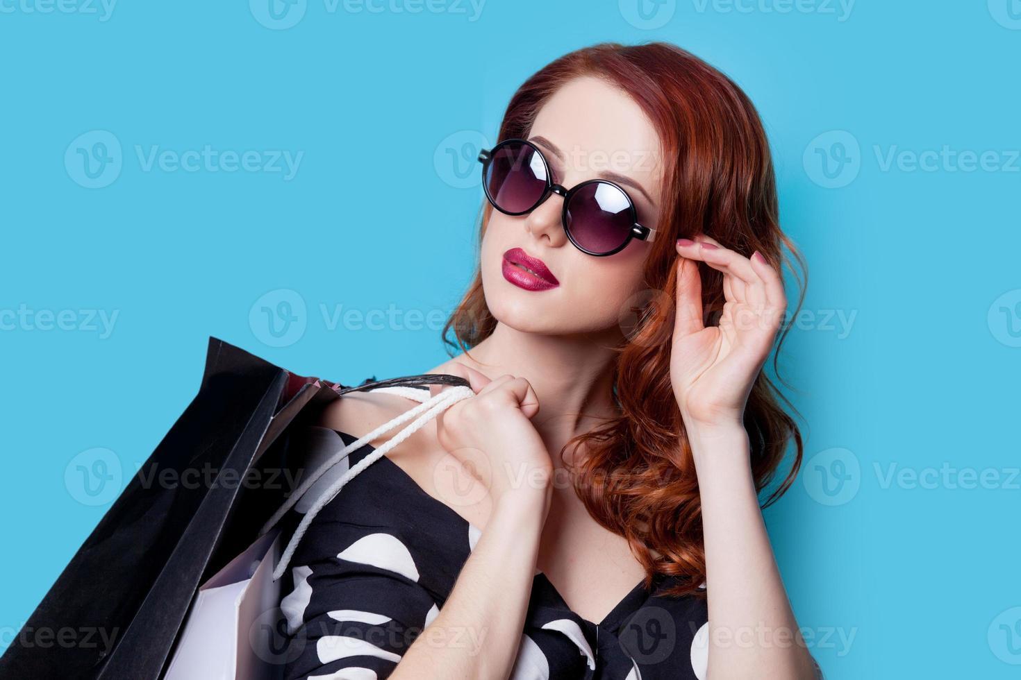 chica en vestido negro con bolsas de compras foto
