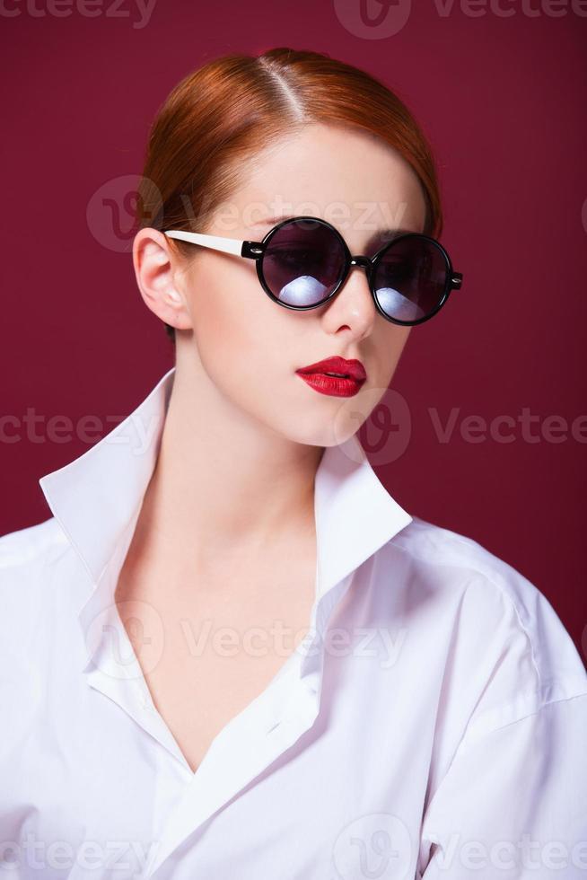 roodharige in zonnebril op rode achtergrond foto