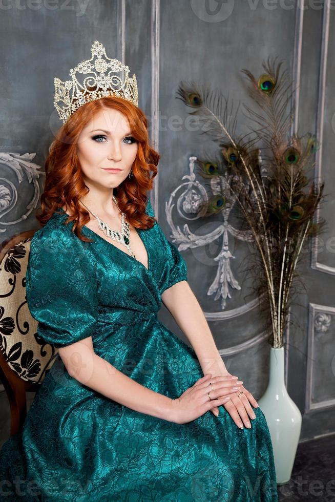 reina, persona real con corona, cabello rojo y vestido verde foto