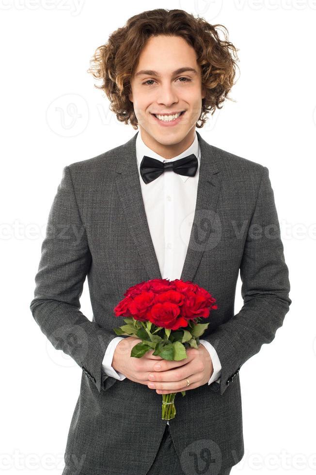 Novio en esmoquin posando con un ramo foto