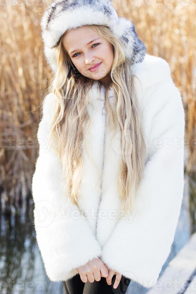 Cute little girl in winter clothes outdoors photo