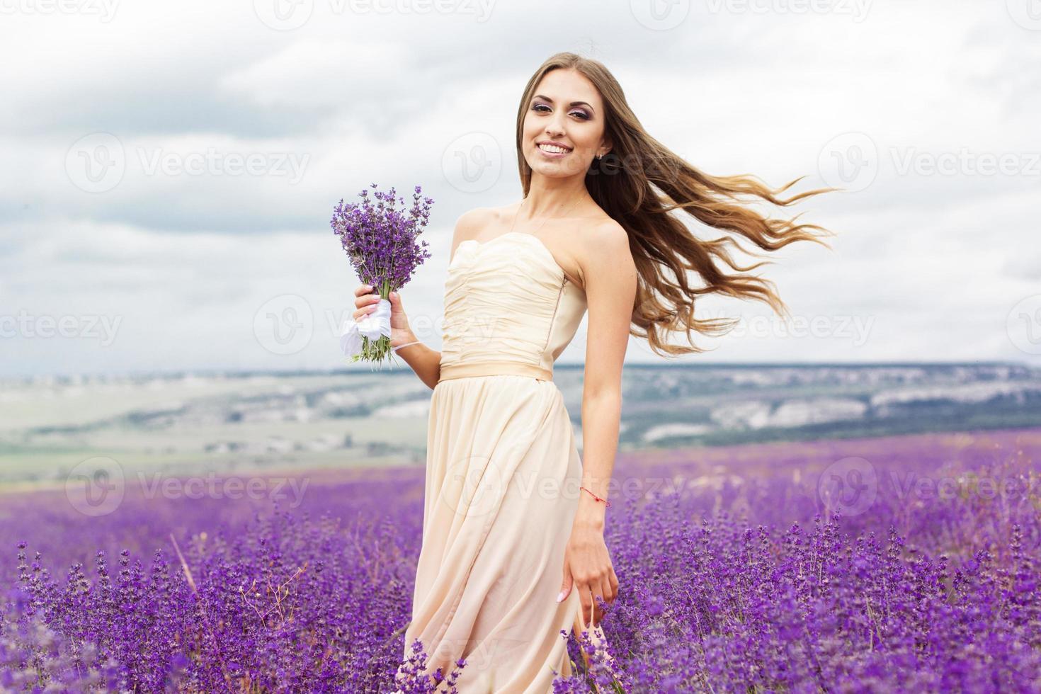 bella ragazza sorridente indossa abito al campo di lavanda viola foto