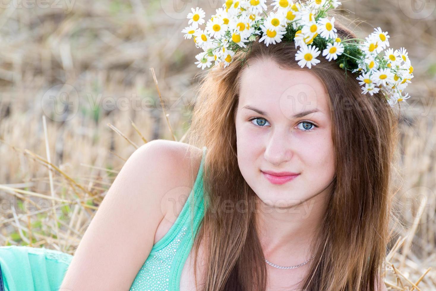 Jovencita con una corona de margaritas en campo foto