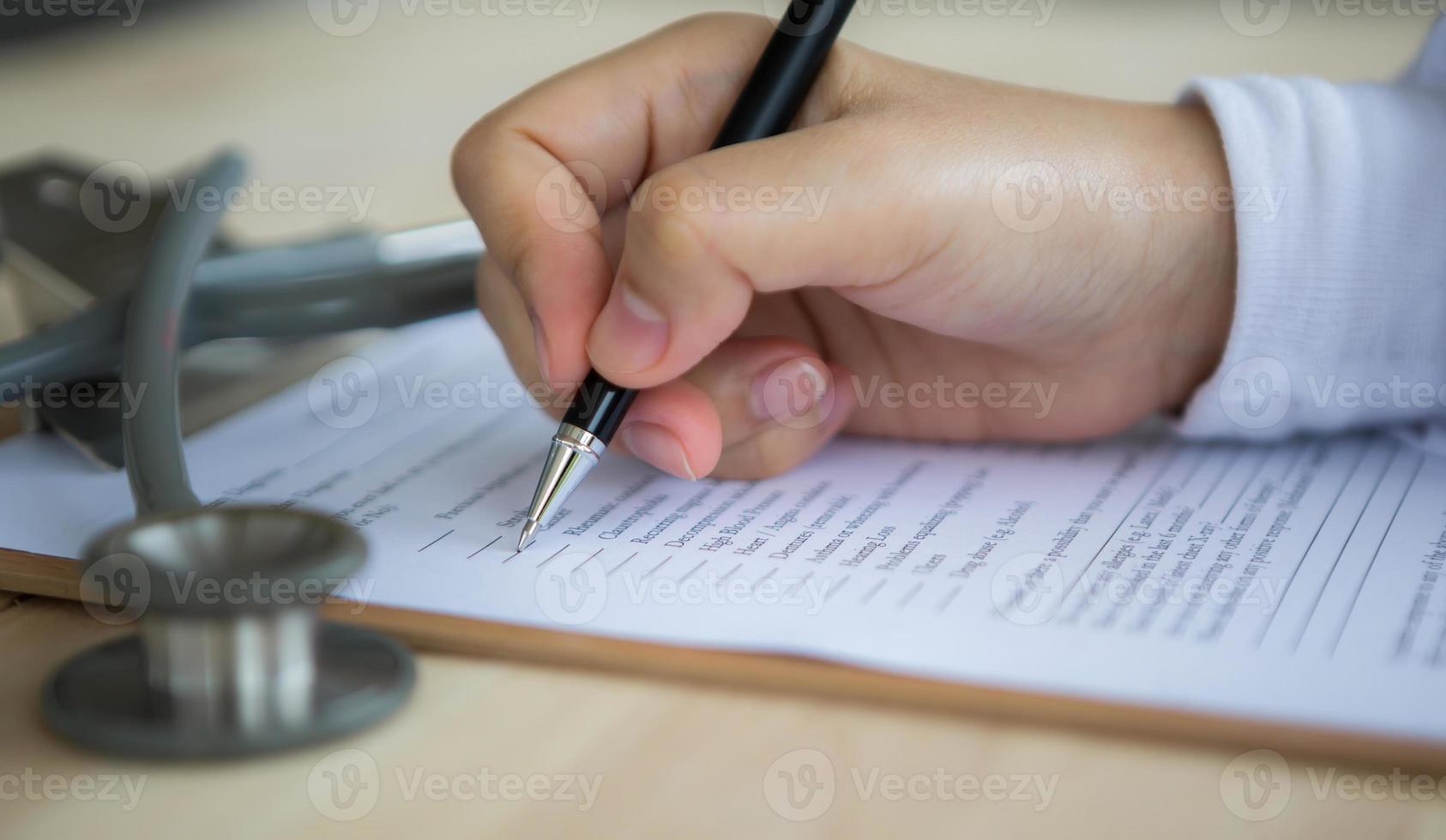 mano del medico scrivendo su prescrizione medica foto