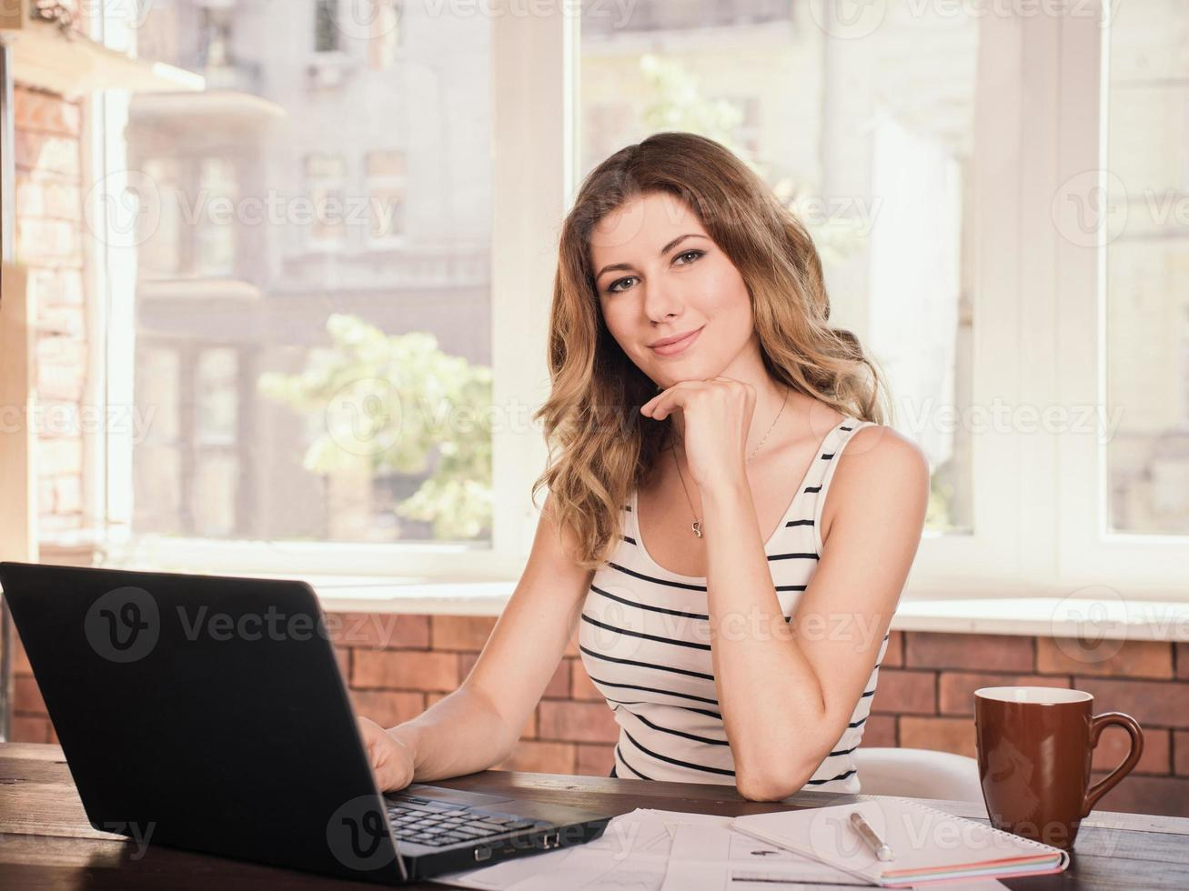 Business woman working on laptop computer at home office photo