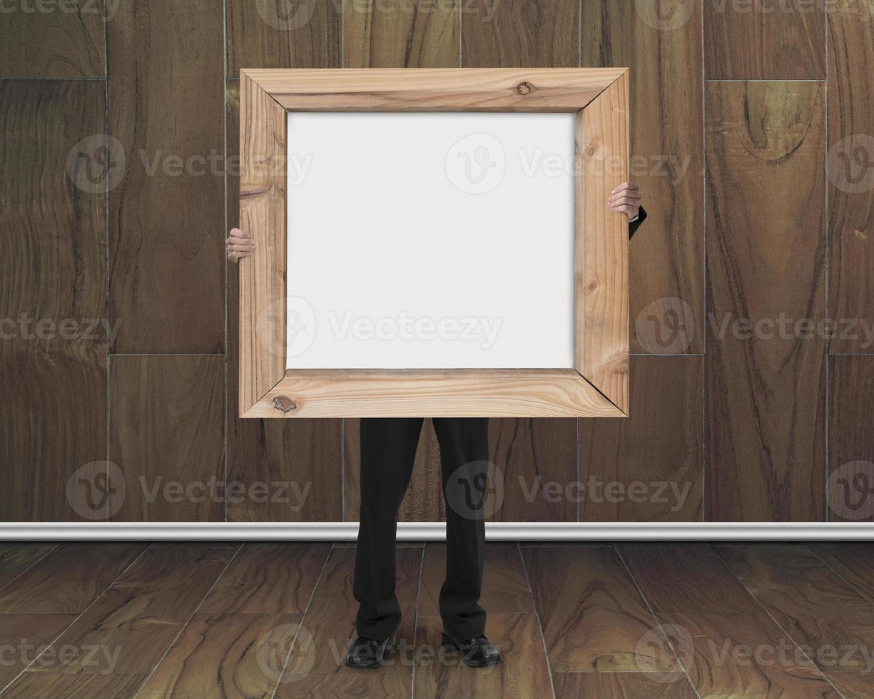 businessman holding blank whiteboard with wood frame in wooden r photo