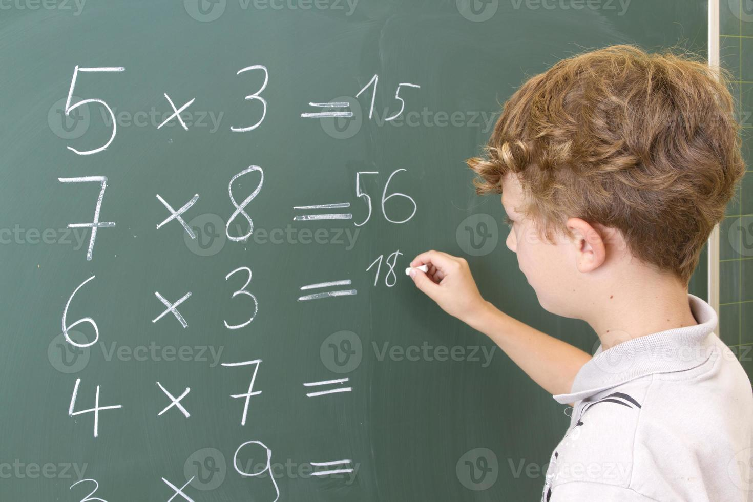 Young boy doing math lesson sums on blackboard photo