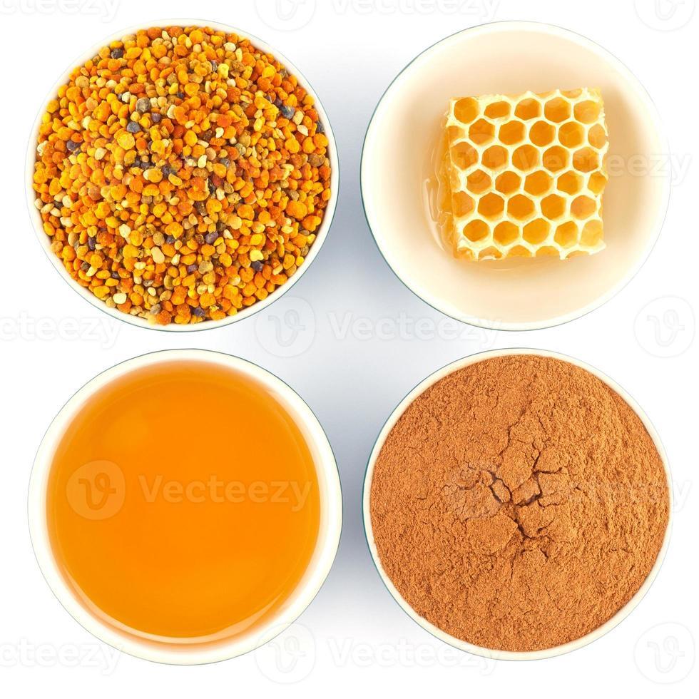 miel, panal, polen y canela en tazones foto
