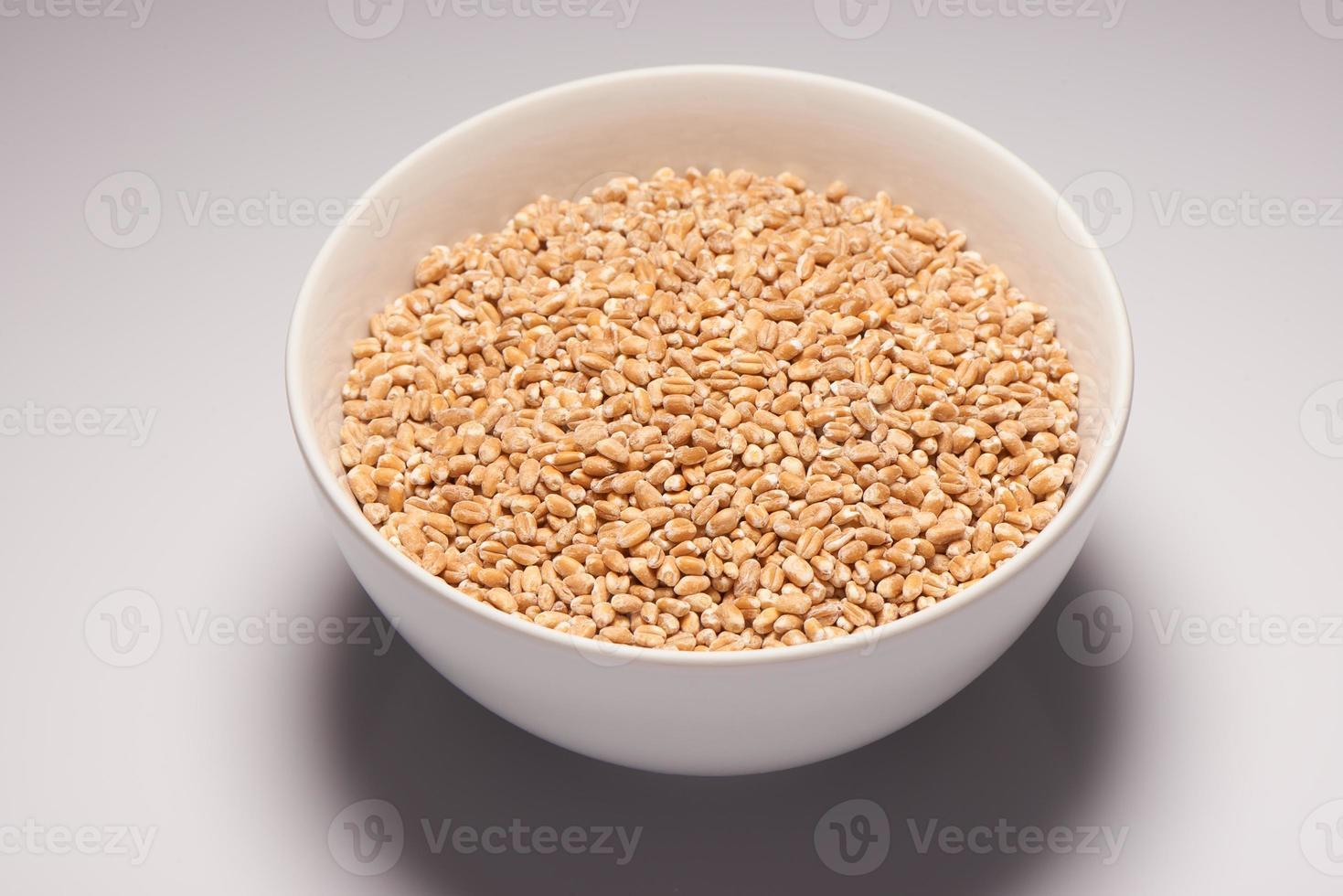 Barley in white ceramic bowl on white background photo