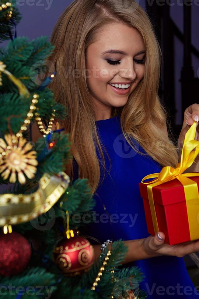 woman under new year tree with christmas present photo