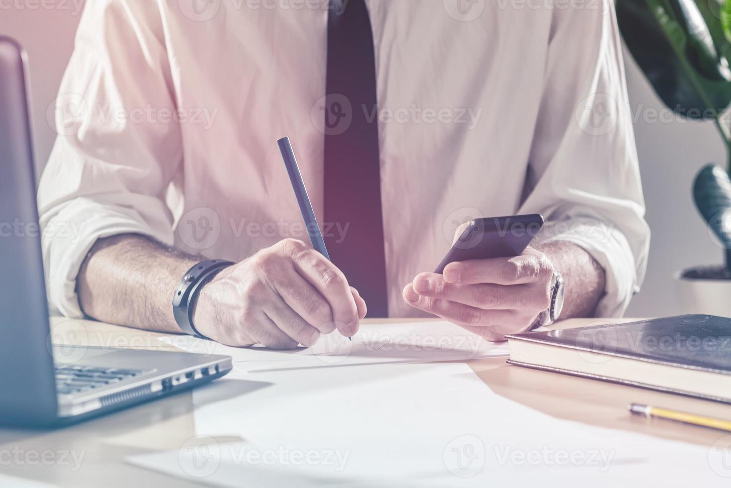 Businessman writing notes from mobile phone at office desk photo