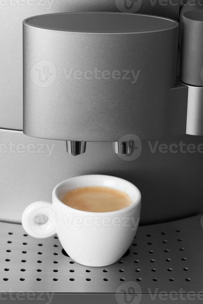 Small cup of espresso in modern automatic coffee machine photo
