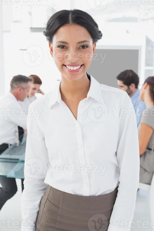 Smiling businesswoman and her colleagues photo