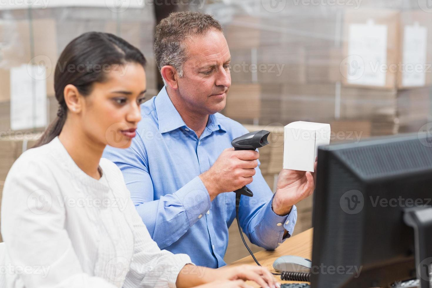 Manager scanning box while his colleague typing on laptop photo