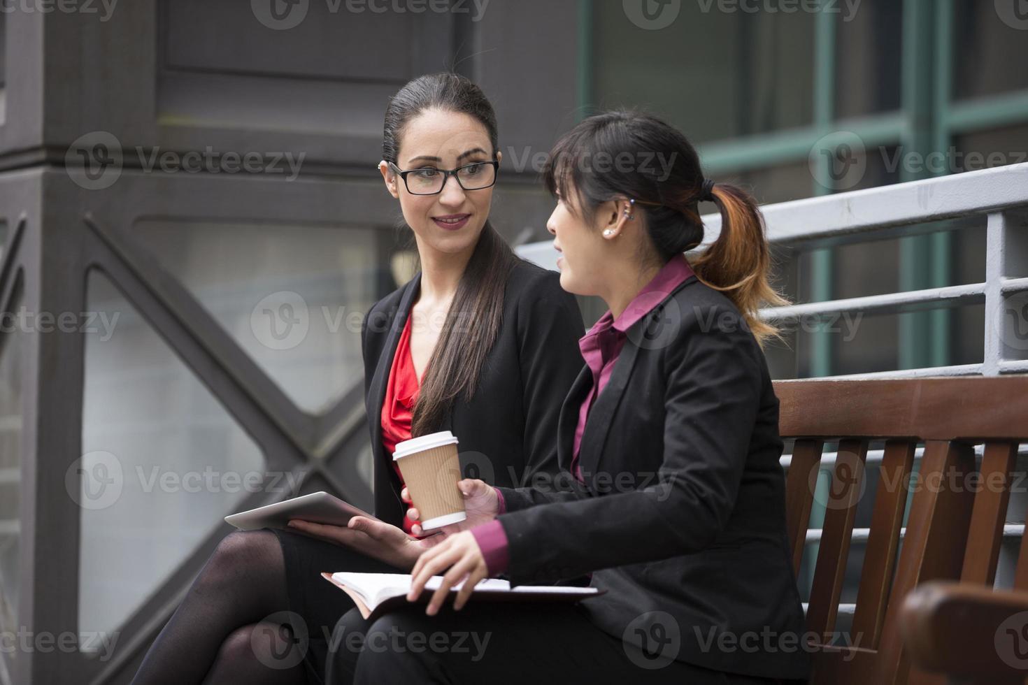 Dos empresarias con tableta digital en un entorno urbano moderno. foto