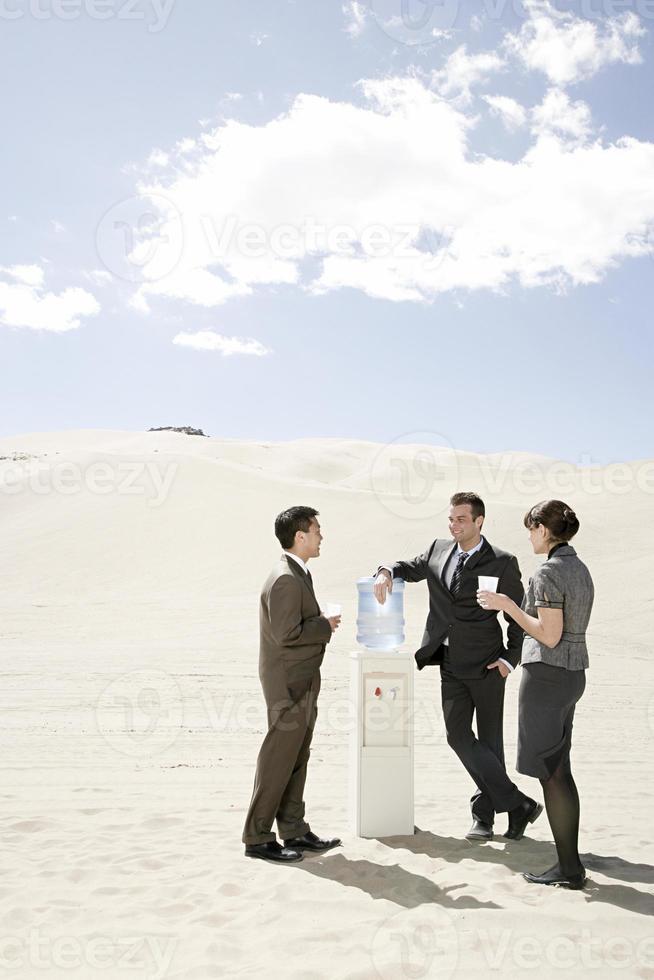 People around water cooler in the desert photo