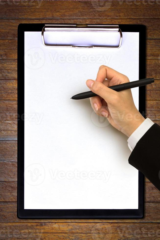 Hand writing in open paper on table photo