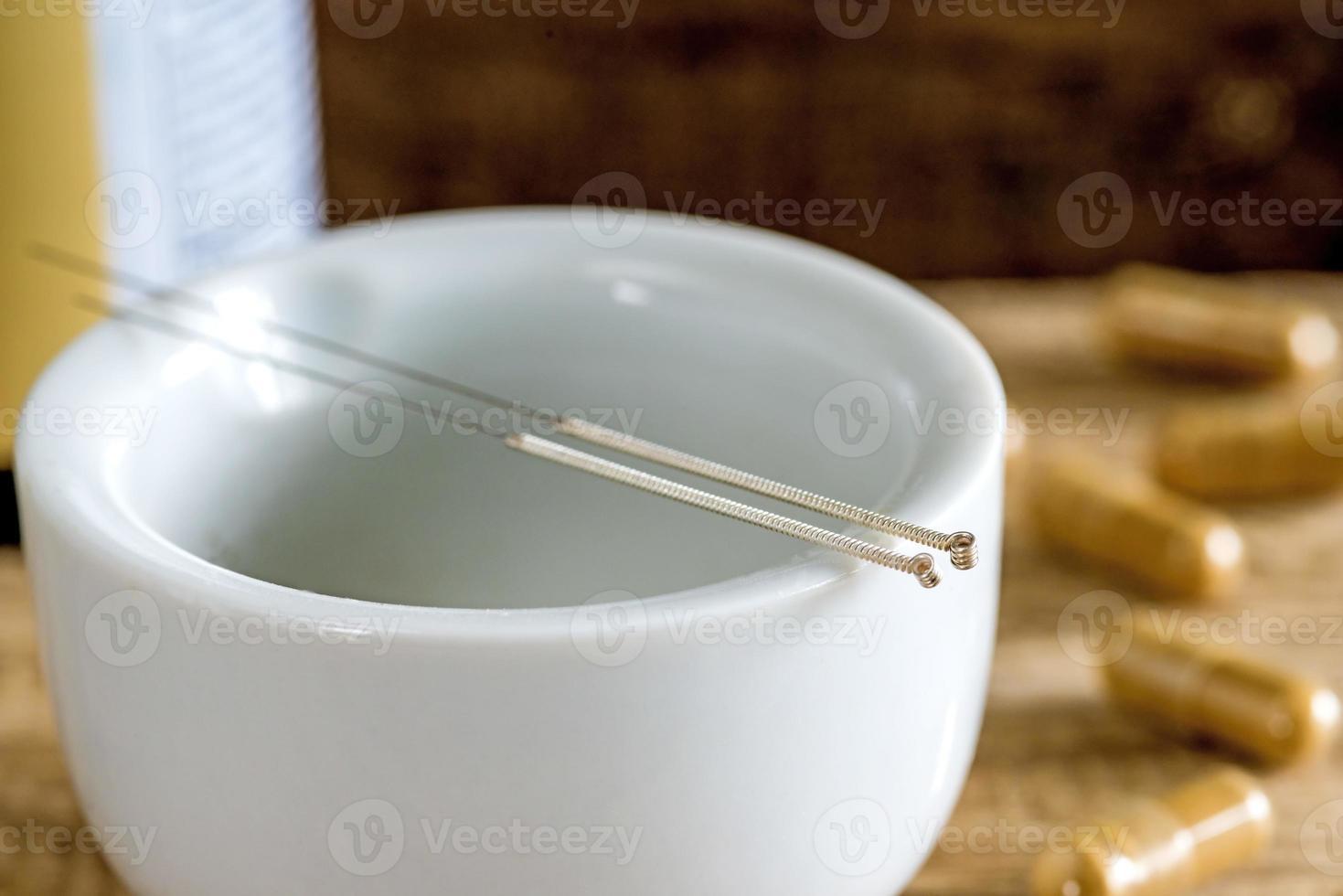 agujas de acupuntura con mortero y pastillas herbales chinas foto