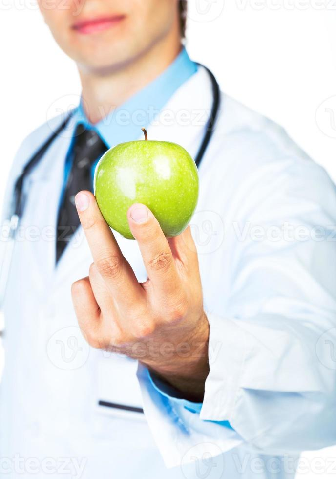 Doctor's hand holding a fresh green apple close-up on white photo