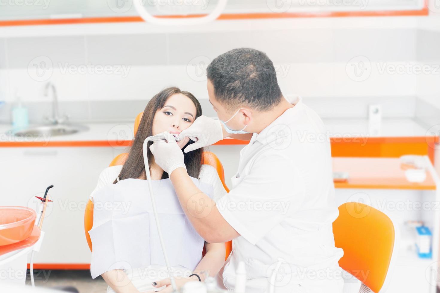dentista médico trata dientes paciente niña en consultorio dental foto