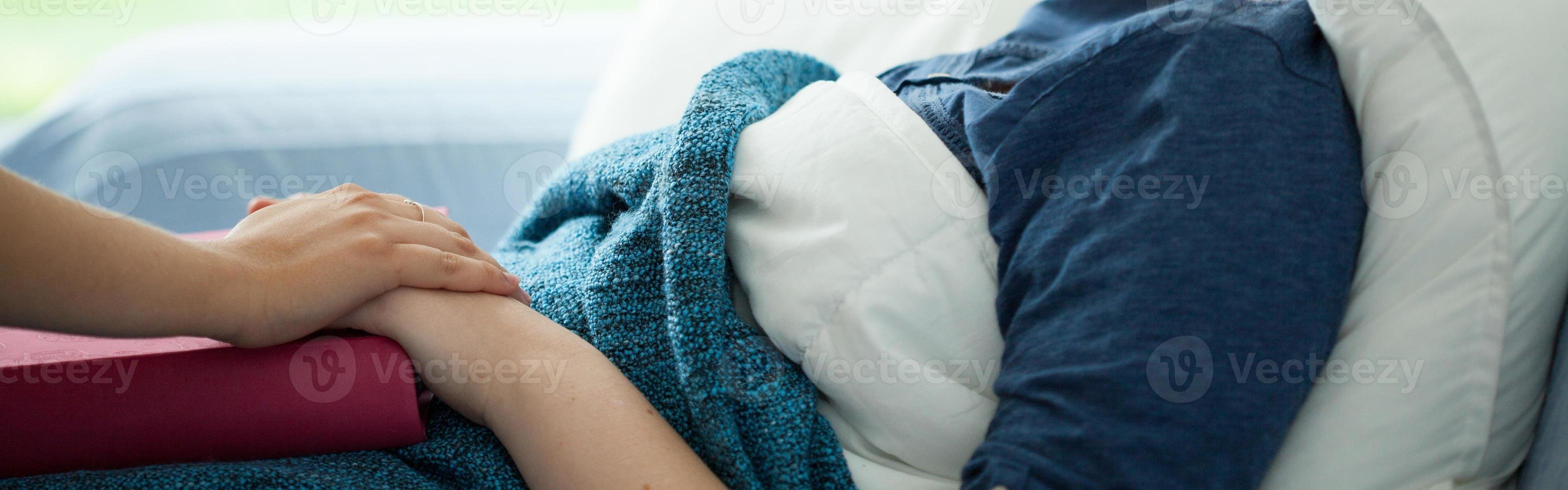 Woman lying in bed being handheld by another person photo