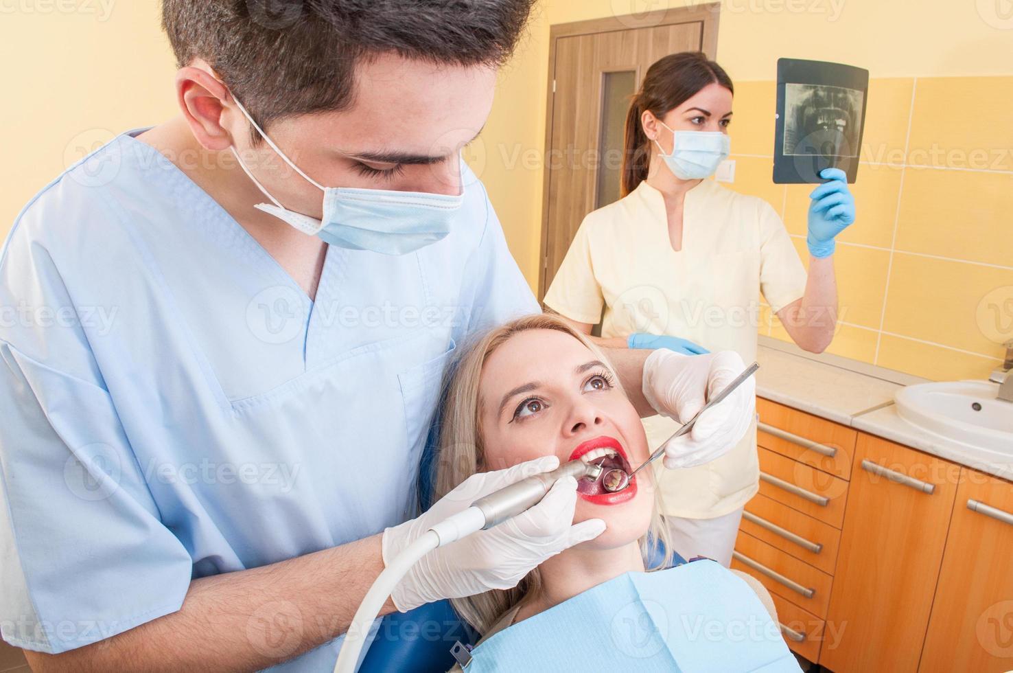 Hermosa mujer paciente en consultorio o gabinete de dentista foto