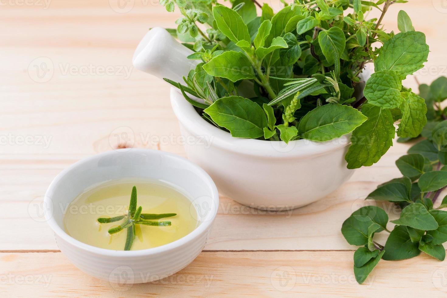 cuidado de la salud alternativa a base de hierbas frescas en mortero blanco foto