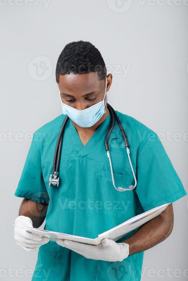 médico negro atento mirando en historia clínica contra b gris foto