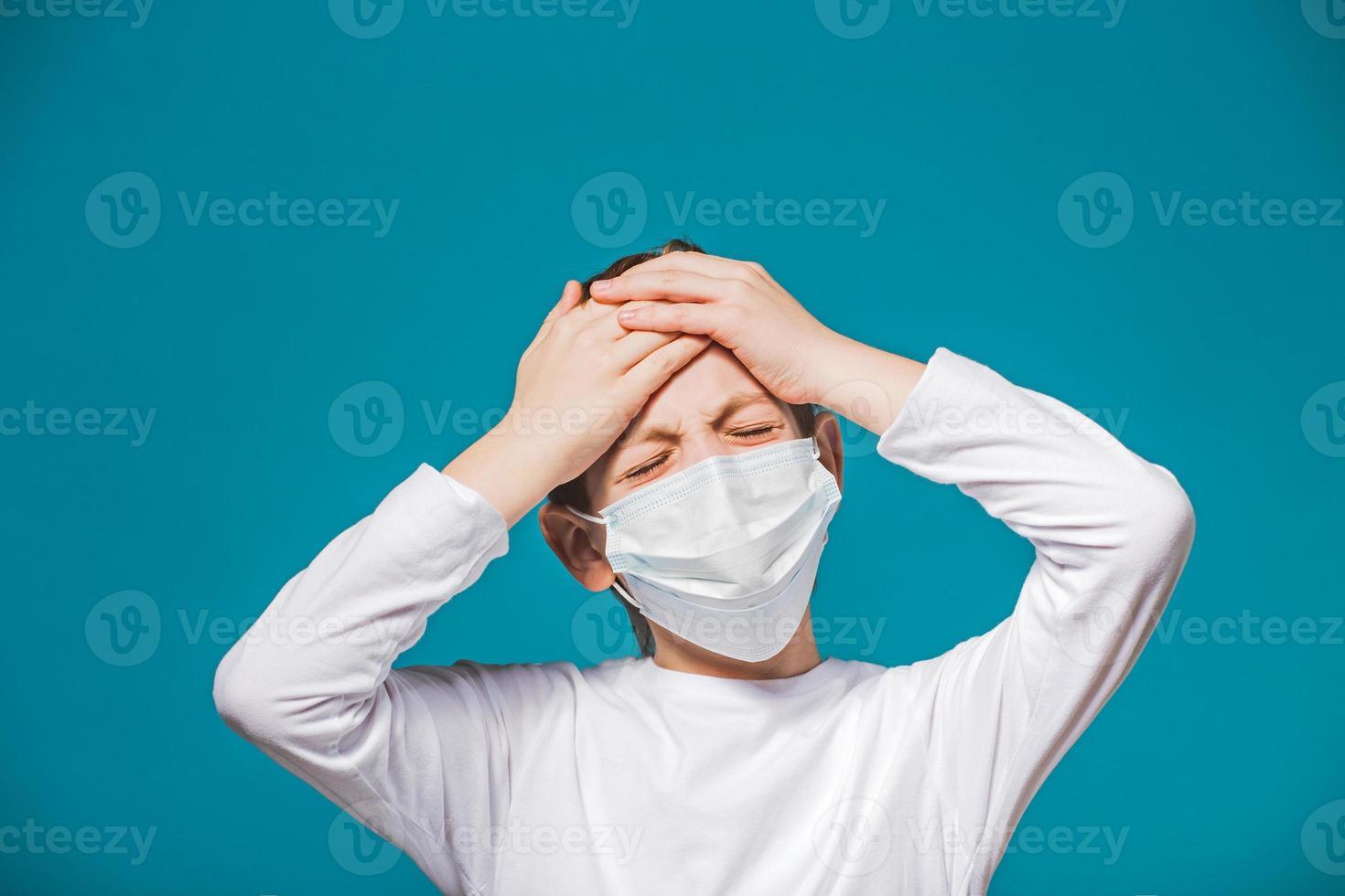 Boy wearing protection mask having headache photo