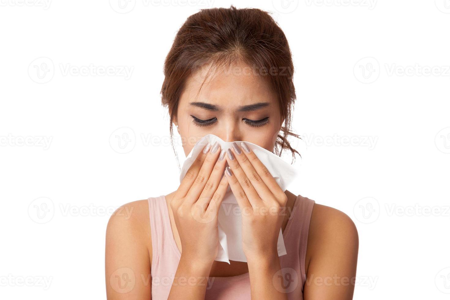 chica bastante asiática se resfrió. estornudar en el tejido. foto